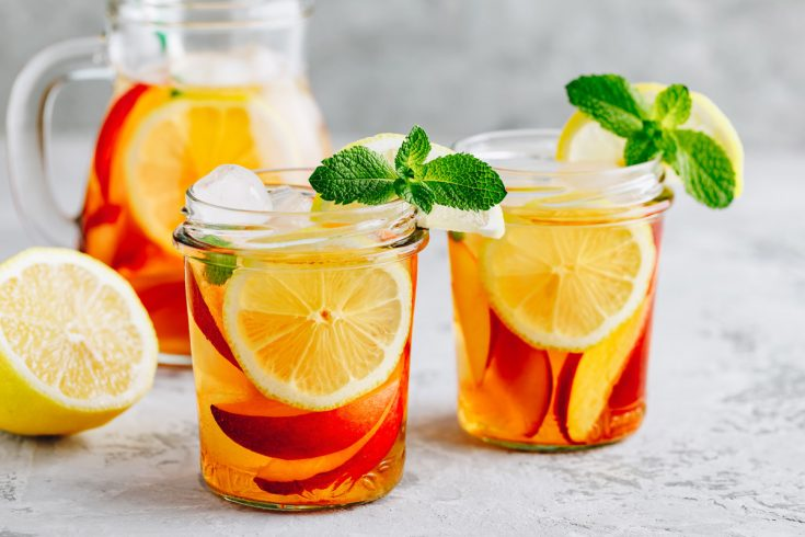Two glasses of peach iced tea and a lemon