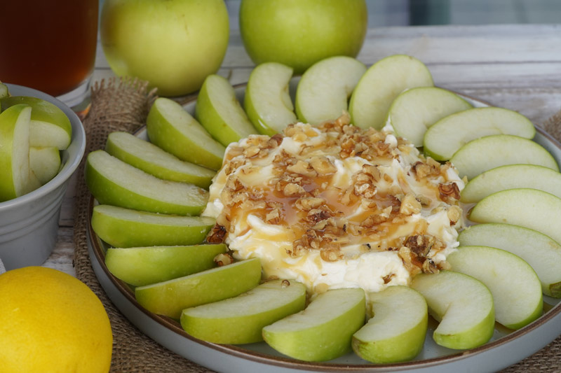Caramel apple dip with a circle of green apples around it